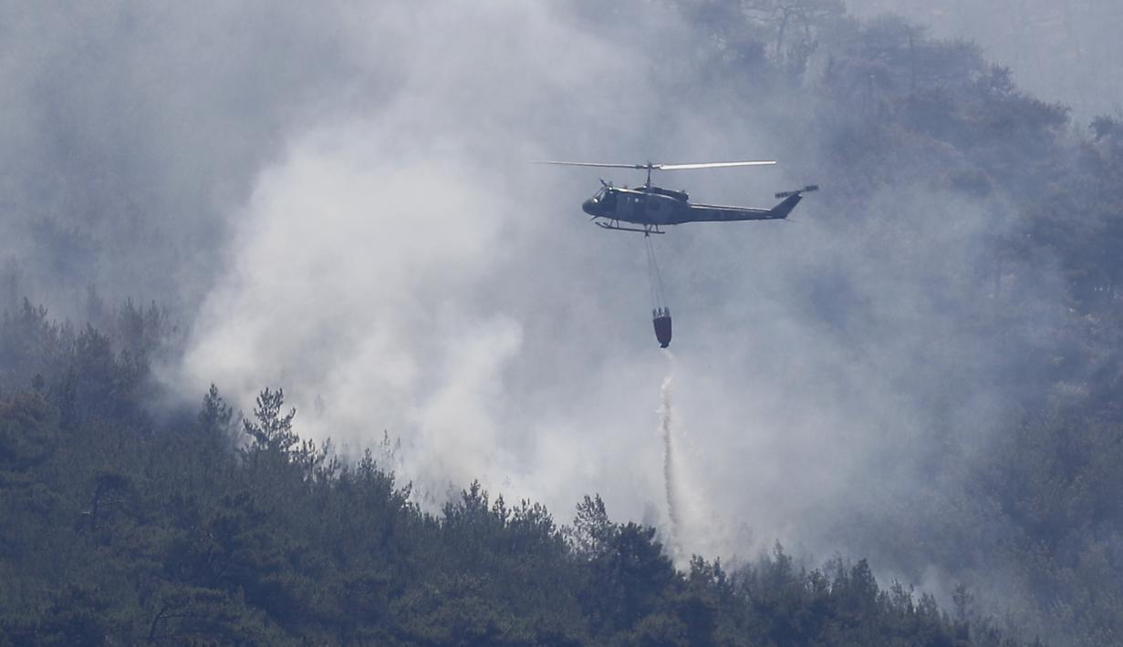 Helikopter tentara Lebanon menjatuhkan air di atas kebakaran hutan, di desa Qobayat, Lebanon, Kamis (29/7/2021). Petugas pemadam kebakaran Lebanon berjuang di hari kedua untuk mengatasi kebakaran hutan di utara negara itu yang telah menyebar ke seluruh perbatasan ke Suriah. (AP Photo/Hussein Malla)