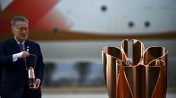 Presiden Olimpiade Tokyo 2020, Yoshiro Mori, membawa api untuk obor Olimpiade Tokyo 2020 saat tiba dari Yunani di Pangkalan Udara Matsushima, Jepang, Jumat (20/3). Di tengah pandemi virus corona Covid-19, prosesi menuju Olimpiade Tokyo 2020 masih terus berjalan. (AFP/Philip Fong)