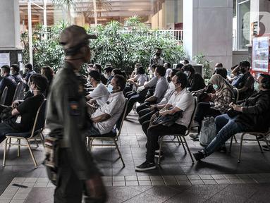 Jurnalis duduk antre untuk memverifikasi data sebelum mengikuti vaksinasi Covid-19 di Balai Kota, Jakarta, Senin (29/3/2021). Pemprov DKI Jakarta bekerja sama dengan Dewan Pers menggelar vaksinasi Covid-19 bagi 5.200 awak media. (merdeka.com/Iqbal S. Nugroho)