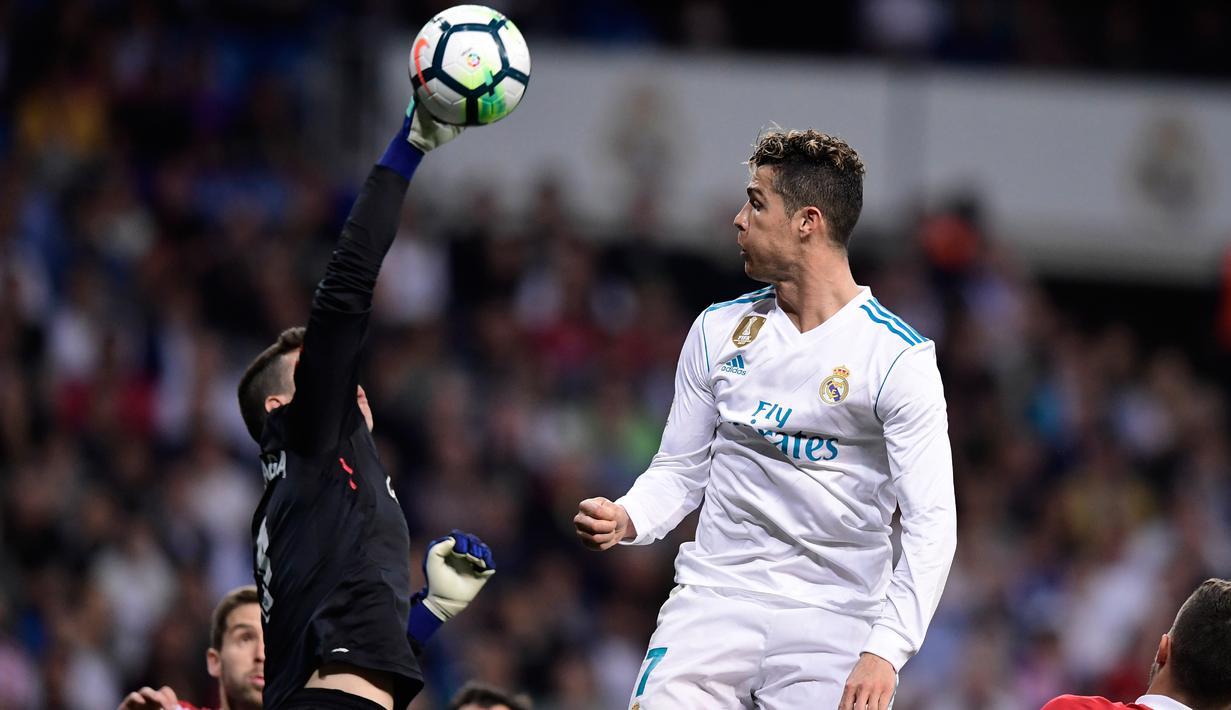 Kiper Kepa Arrizabalaga Revuelta berusaha menepis bola sundulan Cristiano Ronaldo di stadion Santiago Bernabeu, Madrid (18/4). Kepa Arrizabalaga resmi diboyong Chelsea dari Athletic Bilbao. (AFP Photo/Javier Soriano)