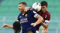 Pemain AC Milan, Alessio Romagnoli, duel udara dengan striker AS Roma, Edin Dzeko, pada laga Serie A di Stadion San Siro, Minggu (28/6/2020). AC Milan menang 2-0 atas AS Roma. (AP/Spada)