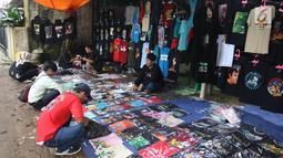 Penggemar Iwan Fals memilih kaos yang dijajakan pedagang di luar lokasi Konser Situs Budaya, kawasan Depok, Jawa Barat, Sabtu (3/3). Dalam Konser kali ini, Iwan Fals dan Band berkolaborasi dengan beberapa musisi. (Liputan6.com/Arya Manggala)