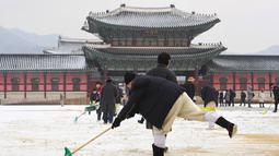Pekerja membersihkan salju di istana Gyeongbokgung setelah salju turun Seoul, Korea Selatan (15/2). Istana ini hancur pada saat invasi Jepang ke Korea tahun 1592-1598dan dibangun lagi selama tahun 1860-an. (AFP Photo/Jung Yeon-je)