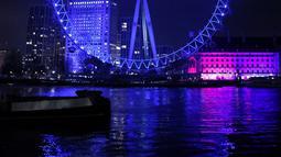 Cahaya biru menerangi objek wisata London Eye untuk berterima kasih kepada National Health Service (NHS) di London, Kamis (7/1/2021). NHS merupakan sistem layanan kesehatan nasional yang menjadi ujung tombak Inggris dalam memerangi pandemi Covid-19. (Tolga Akmen / AFP)