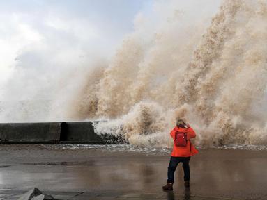 Seorang wanita mengambil gambar ombak yang disebabkan badai Eleanor di sepanjang pinggir laut di New Brighton, Inggris barat laut (3/1). Setelah melanda Inggris, badai Eleanor bergerak ke Prancis, Belgia dan Belanda. (AFP Photo/Paul Ellis)