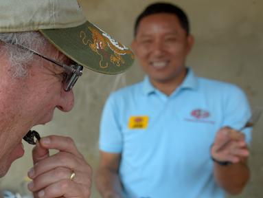 Seorang turis memakan tarantula goreng di wilayah Skun, Provinsi Kampong Cham, Kamboja, 14 Maret 2018. Warga Kamboja terbiasa mengonsumsi tarantula goreng sebagai camilan. (TANG CHHIN Sothy / AFP)