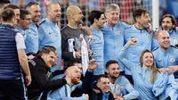 Manajer Manchester City Josep Guardiola (tengah) memegang trofi dan berfoto bersama para pemain serta staf setelah memenangkan pertandingan final Piala Liga Inggris melawan Chelsea di stadion Wembley, London, Minggu (24/2). (AP Tim Ireland)