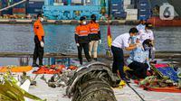 Petugas Komite Nasional Keselamatan Transportasi (KNKT) melakukan identifikasi pesawat Sriwijaya Air SJ 182 di Dermaga JICT, Tanjung Priok, Jakarta, Kamis (21/1/2021). Tim SAR resmi menutup operasi pencarian dan evakuasi korban Sriwijaya Air SJ 182 pada hari ini. (Liputan6.com/Faizal Fanani)