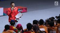 Tunggal putra Indonesia, Jonatan Christie menggigit medali emas usai mengalahkan Chou Tienchen dari ChinesTaipei di final bulutangkis perseorangan Asian Games 2018 di Jakarta, Selasa (28/8). Jonatan unggul 2-1. (Liputan6.com/Helmi Fithriansyah)