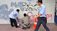 Seorang pejalan kaki melihat kearah petugas saat melakukan pengecatan dinding di kawasan jalan Thamrin, Jakarta, Selasa (22/7/14) (Liputan6.com/Faizal Fanani)