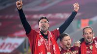 Pelatih Liverpool, Jurgen Klopp, merayakan trofi juara Premier league 2019-2020 di Stadion Anfield, Kamis (23/7/2020) dini hari WIB. Prosesi angkat trofi juara ini dilakukan usai pertandingan Liverpool melawan Chelsea. (AFP/Laurence Griffiths/pool)