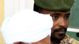 Mantan Presiden Sudan, Omar al-Bashir, dikawal saat keluar dari penjara menuju kantor kejaksaan dalam penyelidikan korupsi di ibu kota Khartoum, Minggu (16/6/2019). Bashir menempuh perjalanan dari penjara Kober menuju kantor jaksa penuntut diiringi konvoi bersenjata lengkap. (Yasuyoshi CHIBA/AFP)
