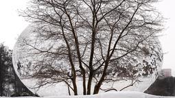 """Patung """"Cloud Gate"""" yang dilapisi salju dan berlapis salju dari Sculptor Anish Kapoor menjadi latar belakang pohon tandus Kamis, 4 Februari 2021, saat pengunjung memasuki Chicago's Millennium Park di awal badai salju lainnya. (AP Photo/Charles Rex Arbogast)"""