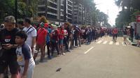 Sejumlah suporter yang ingin menyaksikan laga Indonesia kontra China pada final bulutangkis beregu putra Asian Games 2018 memilih tetap mengantre demi mendapatkan tiket pertandingan. (Bola.com/Benediktus Gerendo Pradigdo)