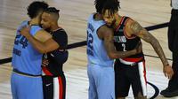 Ekspresi pemain Portland Trail Blazers dan Memphis Grizzlies berpelukan selepas laga play-in NBA di The Field House, Florida, Minggu (16/8/2020) pagi WIB. (Kevin C. Cox/Getty Images via AFP)