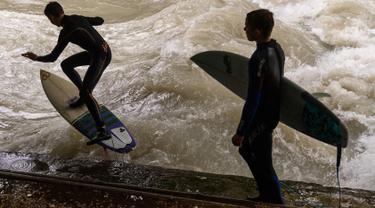 """Peselancar meniti ombak saat bermain """"surfing"""" di sungai buatan Eisbach yang terletak di English Garden Munich, Jerman pada 28 Mei 2019. Aliran air sungai Sungai Eisbach yang memiliki lebar 12 meter ini berasal dari Sungai Isar. (Photo by Peter Kneffel/dpa/AFP)"""