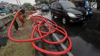 Pekerja merapikan kabel jaringan utilitas ke dalam tanah di kawasan Kemayoran, Jakarta, Minggu (14/1). PT PLN Disjaya akan menertibkan kabel listrik yang ada di tiang-tiang dengan menanam kabel di bawah tanah. (Liputan6.com/Immanuel Antonius)