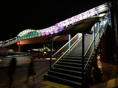 Lampu yang bisa berganti-ganti warna menghiasi jembatan penyeberangan orang (JPO) di kawasan Jakarta Timur, Kamis (27/12). Jembatan ini dihiasi warna warni lampu dengan fasilitas lift untuk para disabilitas menyeberang jalan. (Merdeka.com/Imam Buhori)