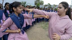 Juara karate internasional Muslim India, Syeda Falak mengajari teknik pukulan dalam bela diri kepada seorang siswi di Telangana Minorities Residential Girls School di Hyderabad, India (17/6). (AFP Photo/Noah Seelam)