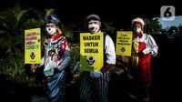 Angggota Komunitas Aku Badut Indonesia (ABI) melakukan aksi kampanye penggunaan di kawasan Cilandak, Jakarta Selatan, Senin (12/7/2021). Selain itu, mereka juga membagi-bagikan masker secara gratis bagi para pengendara motor yang melintas. (Liputan6.com/Johan Tallo)