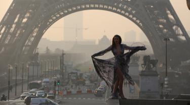 Seorang model cantik berpose di depan menara Eiffel saat matahari terbit dalam sesi pemotretan, Paris (11/3/2016). (AFP/Ludovic MARIN)