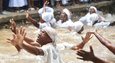 Pengikut Voodoo Haiti mandi di kolam suci selama upacara voodoo di Souvenance, Haiti (4/1). Sejumlah ritual digelar para pengikuti Voodoo Haiti ini selam akhir pekan perayaan Paskah. (AFP/Hector Retamal)