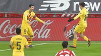 Striker Barcelona, Lionel Messi (kiri) melakukan selebrasi bersama gelandang Pedri usai mencetak gol kedua timnya ke gawang Athletic Bilbao dalam laga lanjutan Liga Spanyol 2020/21 di San Mames Stadium, Bilbao, Rabu (6/1/2021). Barcelona menang 3-2 atas Athletic Bilbao. (AFP/Ander Gillenea)
