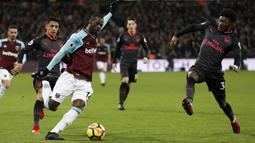 Pemain West Ham, Pedro Obiang (kiri) membuang bola dari kejaran para pemain Arsenal pada lanjutan Premier League di London stadium, London, (13/12/2017). Arsenal bermain imbang 0-0 dengan West Ham. (AP/Kirsty Wigglesworth)