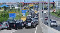 Kendaraan antre menuju pintu keluar Tol Brebes Timur, Jawa Tengah, Sabtu (23/12). Libur Natal 2017, arus lalu lintas yang akan keluar dari pintu Tol Brebes Timur terjadi kepadatan. (Liputan6.com/Helmi Fithriansyah)