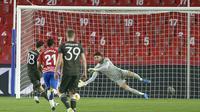 Gelandang Manchester United, Bruno Fernandes (kiri) mencetak gol kedua timnya melalui eksekusi penalti ke gawang Granada dalam laga leg pertama perempatfinal Liga Europa 2020/2021 di Nuevo Los Carmenes Stadium, Granada, Kamis (8/4/2021). Manchester United menang 2-0. (AFP/Cristina Quicler)