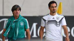 Pelatih Jerman, Joachim Loew (kiri) dan bek Matts Hummels saat menghadiri sesi pelatihan tim di Munich, Jerman Selatan, (4/9). Jerman akan menghadapi Prancis di UEFA Nations League pada 6 September 2018. (AFP Photo/Christof Stache)