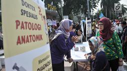 Warga berkonsultasi dengan dokter sebelum diperiksa tensi saat car free day di kawasan Bundaran HI, Jakarta, Minggu (18/11). Kegiatan periksa tensi secara gratis ini dalam rangka memperingati Hari Patologi Internasional. (Merdeka.com/Iqbal S. Nugroho)