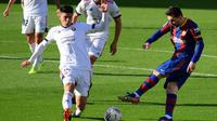 Penyerang Barcelona, Lionel Messi, melepaskan tembakan saat dikawal ketat oleh bek Osasuna, Facundo Roncaglia, pada laga pekan ke-11 La Liga 2020-2021 di Camp Nou, Minggu (29/11/2020) malam WIB. (AFP/Lluis Gene)