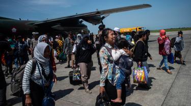 Seorang wanita membawa anaknya ketika mereka tiba di Surabaya, Kamis (4/10). Banyak anak-anak yang terpisah dari keluarganya setelah bencana gempa-tsunami melanda Palu dan Donggala pada 28 September. (AFP Photo/Juni Kriswanto)