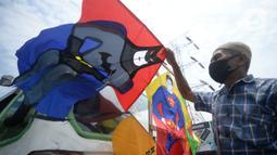 Abdul Karim (65) sopir angkotan Jurusan Ciputat-Muncul merapikan layangan hias di Pingir Jalan Siliwangi, Tangerang Selatan, Banten, Senin (29/9/2020). Pemberlakuan PSBB DKI Jakarta diperketat untuk menekan penularan Covid-19 berimbas kepada penumpang angkutan umum sepi. (merdeka.com/Dwi Narwoko)