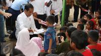 Presiden Joko Widodo (Jokowi) membagi-bagikan buku tulis untuk anak-anak saat meninjau tenda pengungsian korban gempa Aceh di Pidie Jaya, Jumat (9/12). Selain buku tulis, Jokowi juga membagikan kotak pensil kepada warga. (Liputan6.com/Angga Yuniar)