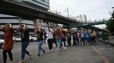 Karyawan call center melindungi kepalanya sambil berjalan saat mengikuti latihan gempa di Manila (14/11/2019). Latihan ini sebagai bagian dari kesiapsiagaan nasional menyusul berbagai gempa yang melanda pulau Mindanao bulan lalu. (AFP Photo/Ted Aljibe)