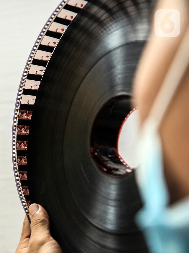 Adul (29) mengecek film seluloid 35mm untuk pertunjukan layar tancap di gudang rumahnya di Jakarta, Rabu (28/4/2021). Bioskop modern telah menyingkirkan keberadaannya sebagai alternatif hiburan warga yang berada di kota ataupun kampung-kampung. (Liputan6.com/Johan Tallo)