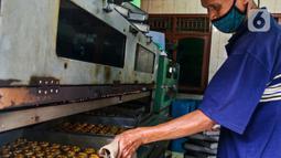 Pekerja memasukkan adonan kue ke oven di industri pembuatan kue kering Pusaka Kwitang, Jakarta, Kamis (30/4/2020). Kue kering yang dijual seharga Rp480 ribu per kaleng itu pada bulan Ramadan tahun ini mengalami penurunan produksi hingga 500 kaleng akibat pandemi COVID-19. (Liputan6.com/Johan Tallo)