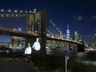 Gambar korban diproyeksikan pada Jembatan Brooklyn saat Hari Peringatan COVID-19 di Brooklyn, New York, Amerika Serikat, 14 Maret 2021. Kota New York yang mencatat kematian tertinggi akibat COVID-19 di AS, memberikan penghormatan yang emosional pada para korban yang meninggal. (Kena Betancur/AFP)