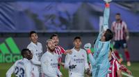Kiper Real Madrid, Thibaut Courtois menepis bola saat bertanding melawan Atletico Madrid pada pertandingan La Liga Spanyol di stadion Alfredo Di Stefano, Spanyol, Minggu (13/12/2020). Madrid menang atas Atletico 2-0. (AP Photo/Bernat Armangue)