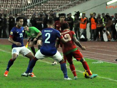 Pemain malaysia, Mahali (tengah) berusaha mengambil bola dari kawalan Pemain Indonesia, Irfan Bachdim (kiri) dalam Laga Piala AFF Suzuki 2012 antara Malaysia vs Indonesia di Stadion Bukit Jalil, Kuala Lumpur, Malaysia. pertandingan berakhir dengan skor 2-