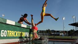 Seorang pelari putri terjatuh ke dalam air saat berlomba di nomor lari halang rintang 3000m dalam kejuaraan atletik AS Terbuka 2015 di Hayward Field, Oregon, AS. (25/6). (Andy Lyons/Getty Images/AFP)