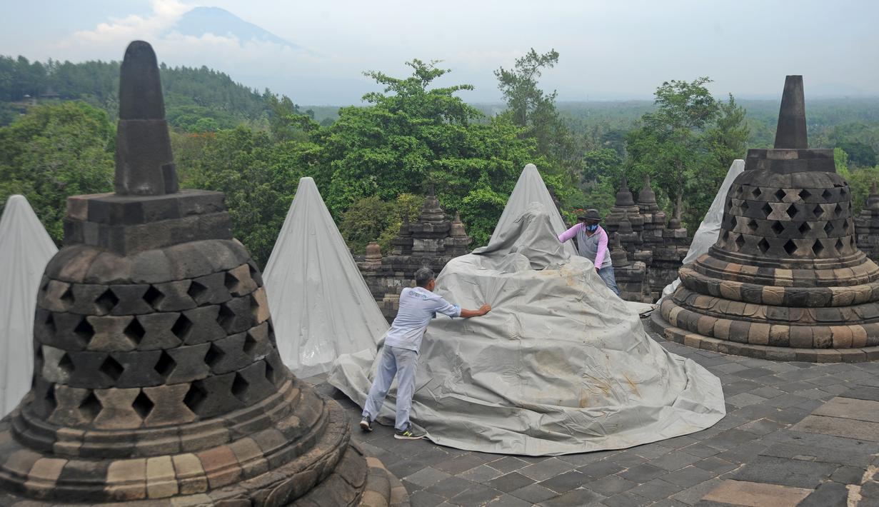 Pekerja menutup stupa di kompleks candi Borobudur, Magelang, Jawa Tengah, Senin (23/11/2020). Penutupan candi Borobudur oleh BKB (Balai Konservasi Borobudur) sebagai langkah antisipasi melindungi batu candi dari abu vulkanik jika Gunung Merapi erupsi. (Photo by Agung Supriyanto/AFP)