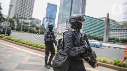Petugas Brimob dengan senjata lengkap berjaga di kawasan Bundara HI, Jakarta, Kamis (24/12/2020). Pengamanan ini dilakukan guna memberikan pengamanan kepada umat nasrani merayakan malam natal di Jakarta. (Liputan6.com/Faizal Fanani)