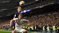 Gelandang Barcelona, Ivan Rakitic berebut bola dengan pemain Real Madrid, Luka Modric pada laga leg kedua semifinal Copa del Rey di Stadion Santiago Bernabeu, Rabu (27/2). Barcelona merebut tiket final Copa del Rey usai menang 3-0. (OSCAR DEL POZO / AFP)