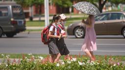 Siswa berjalan di sepanjang jalan saat suhu tinggi mencapai 34 derajat celsius di Pyongyang, Korea Utara, Rabu (21/7/2021). Musim Panas dimulai pada bulan Juni hingga Agustus, dan puncak musim panas adalah bulan Agustus. (KIM Won Jin / AFP)