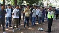 Petugas kepolisian memberikan pelatihan kepada 'Pak Ogah' atau calon Sukarelawan Pengatur Lalu Lintas (supeltas) di Lapangan Banteng, Jakarta, Rabu (23/8). Mereka diwajibkan menjalani serangkaian pelatihan selama lima hari (Liputan6.com/Immanuel Antonius)