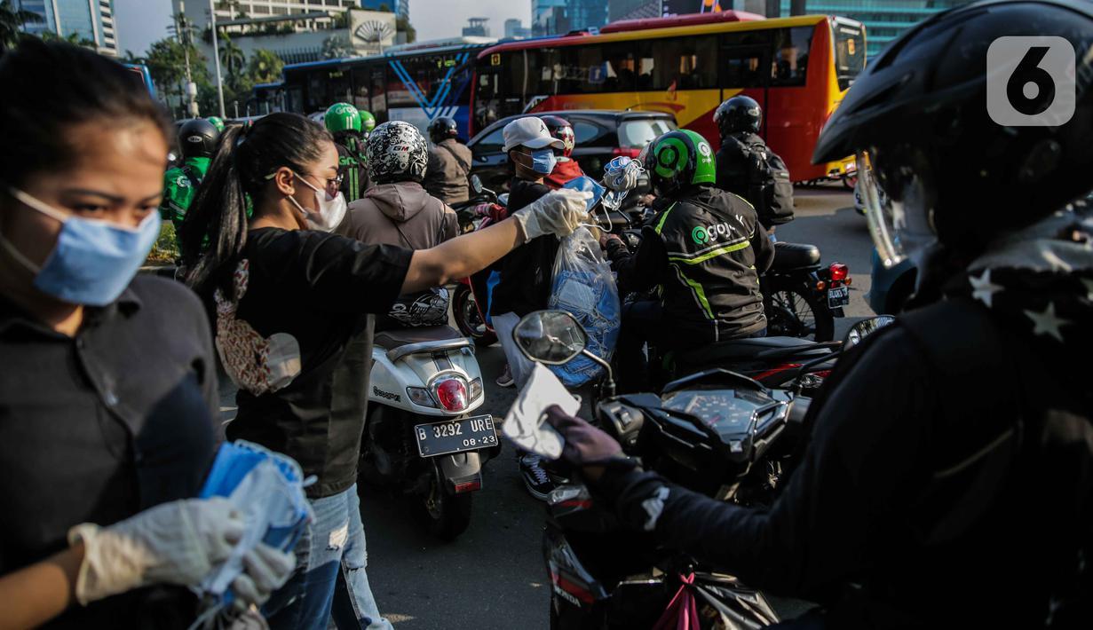 Relawan membagikan masker kepada pengguna jalan di Kawasan Bundaran HI, Jakarta, Selasa (17/3/2020). Sebanyak 3.000 masker dibagikan secara gratis sebagai salah satu bentuk keprihatinan sekaligus berpartisipasi dalam upaya mencegah penyebaran virus corona COVID-19. (Liputan6.com/Faizal Fanani)