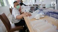Petugas PT KAI (Persero) menata kantong alat tes deteksi COVID-19 dengan metode GeNose C19 di Stasiun Gambir, Jakarta, Rabu (24/3/2021). PT KAI (Persero) menaikkan tarif pemeriksaan tes GeNose C19 dari Rp20 ribu menjadi Rp30 ribu mulai 20 Maret 2021. (Liputan6.com/Faizal Fanani)